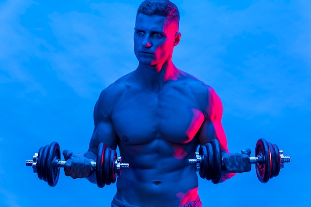Front view of fit shirtless man training with weights