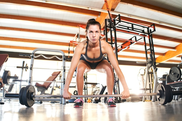 Front view of fit young woman lifting barbells looking focused, working out in a gym alone.