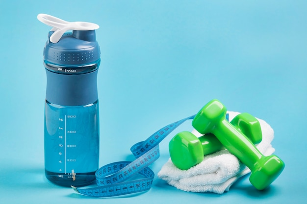 Front view fitness bottle of water and weights