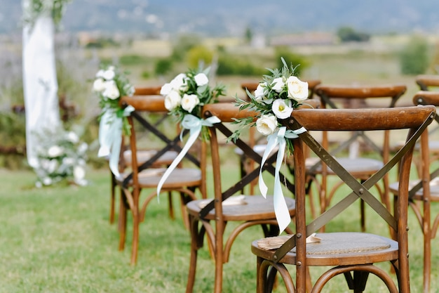 Front view of floral decoration from white eustomas and ruscus of brown chiavari chairs outdoors
