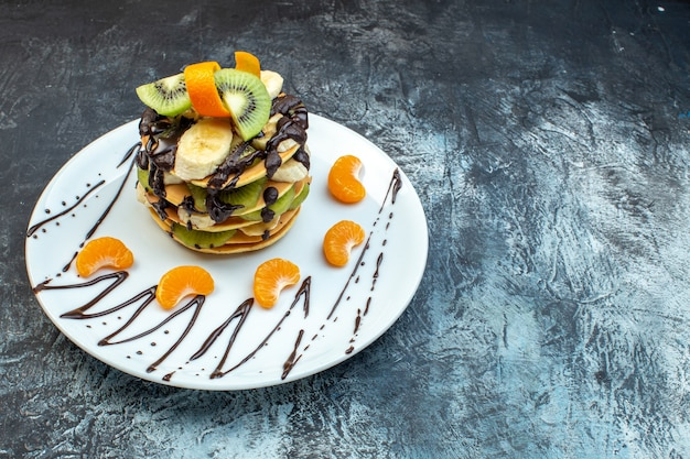 Front view of fluffy american-style pancakes made with natural yogurt and stacked with layers of fruit decorated with chocolate on white plate on ice background