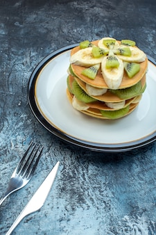 Front view of fluffy american-style pancakes made with natural yogurt and stacked with layers of fruit on plate and cutlery set on ice background with free space