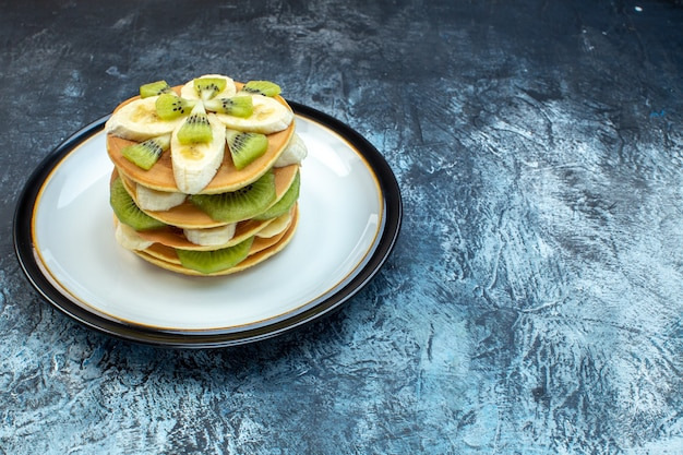 Front view of fluffy american-style pancakes made with natural yogurt and stacked with layers of fruit on plate on the right side on ice background with free space