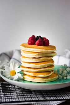Front view fluffy pancakes tower with raspberries