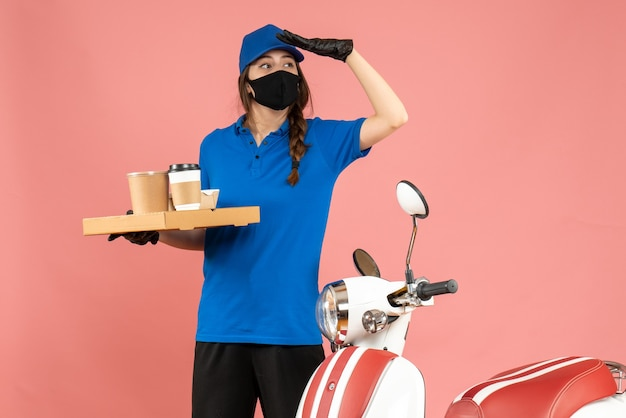 Front view of focused courier girl wearing medical mask gloves standing next to motorcycle holding coffee small cakes on pastel peach color background