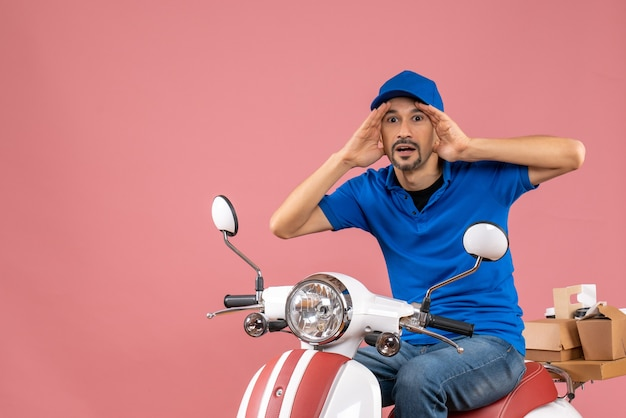 Front view of focused courier guy wearing hat sitting on scooter on pastel peach background