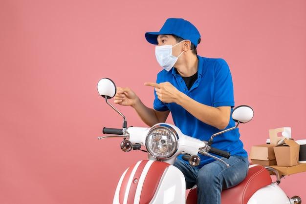 Vista frontale dell'uomo corriere focalizzato in maschera medica che indossa cappello seduto su scooter su sfondo pesca pastello