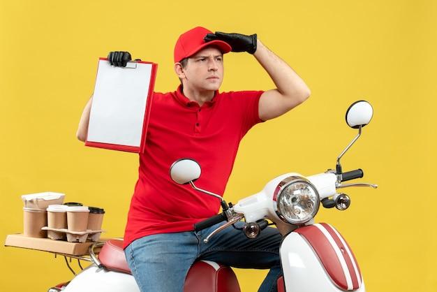 Vista frontale del corriere focalizzato uomo che indossa guanti camicetta e cappello rossi nella mascherina medica che trasporta ordine che si siede sul documento della tenuta dello scooter
