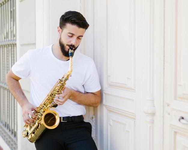 Вид спереди сосредоточены человек играет на саксофоне