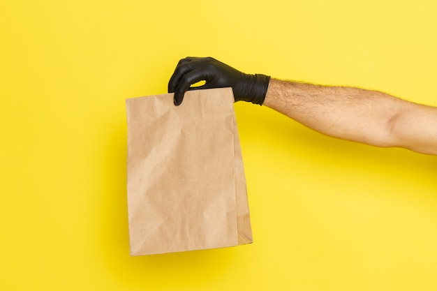 Front view food package holding by male in black gloves on yellow