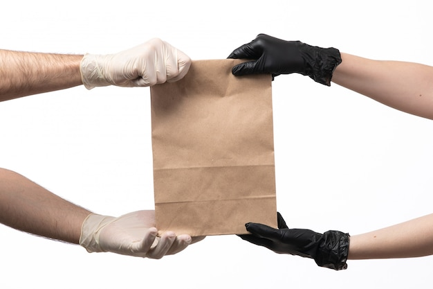 A front view food paper package being delivered from female to male both in gloves on white