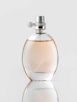 Una bottiglia di profumo vista frontale trasparente sul pavimento bianco