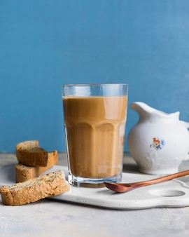 Front view frappe in glass next to slices of bread with seeds
