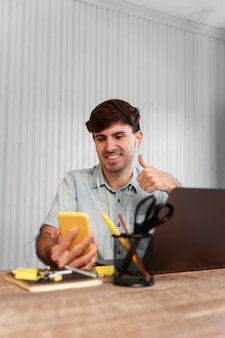 Фрилансер, вид спереди, смотрит на свой телефон в проекте