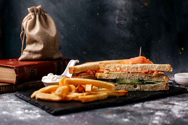 Front view french fries along with sandwiches on the black desk and grey surface