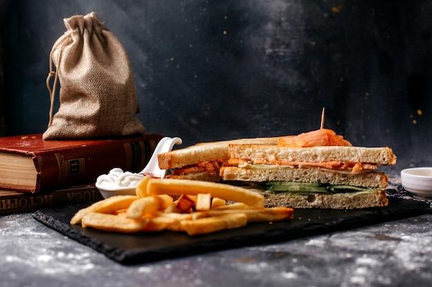 Картофель фри спереди и бутерброды на черном столе и серой поверхности