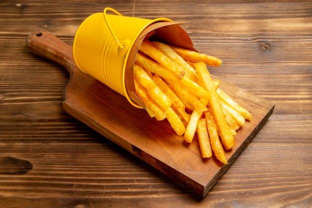 Patatine fritte di vista frontale dentro il piccolo cestino sul pasto marrone dell'hamburger del fast food della patata della scrivania