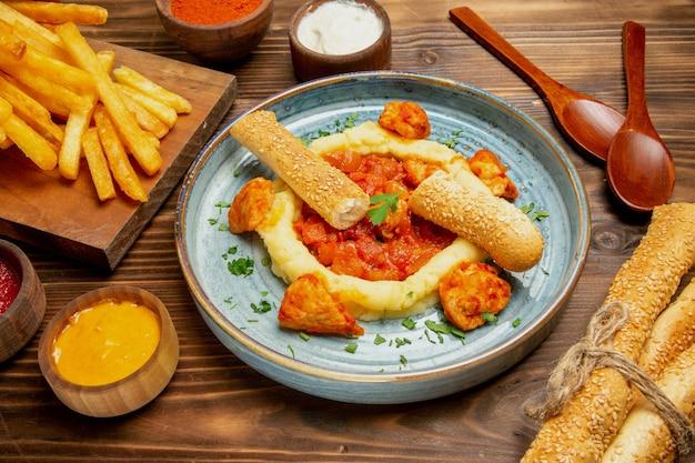 ブラウン デスク ポテト ファーストフード ハンバーガーの食事にチキン スライスとフライド ポテトの正面図