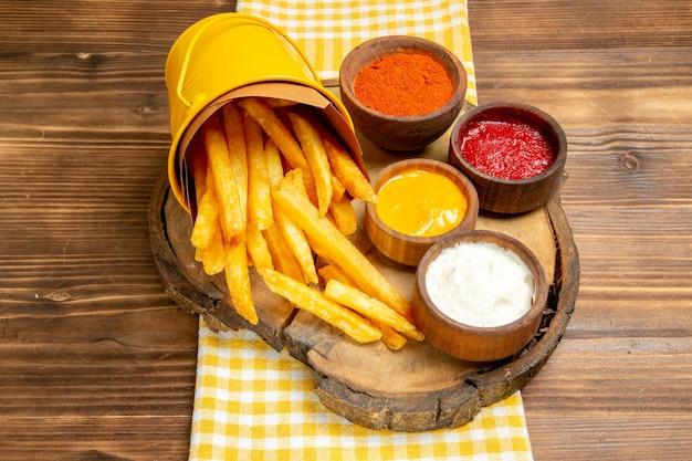 Patatine fritte di vista frontale con condimenti sul pasto del pranzo dello spuntino della patata dello scrittorio di legno