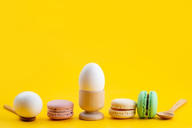 A front view french macarons along with boiled eggs on yellow, biscuit cake sugar candy food