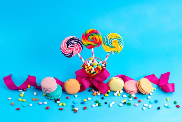A front view french macarons along with candies and lollipops colorful candies all on blue