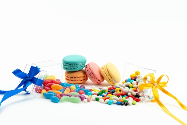 A front view french macarons along with colorful candies on white, biscuit cake color