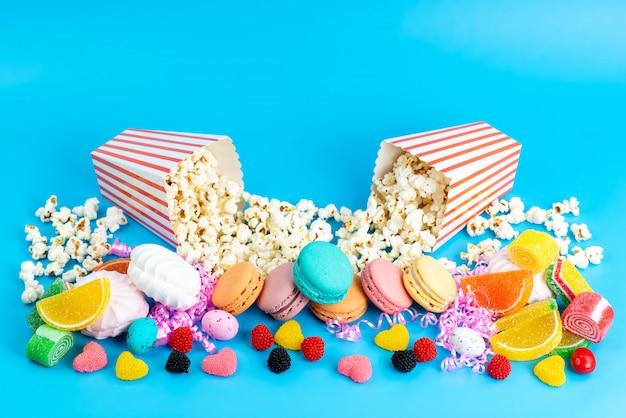 Macarons francesi di una vista frontale insieme ai popcorn della caramella gommosa e molle delle marmellate sull'azzurro