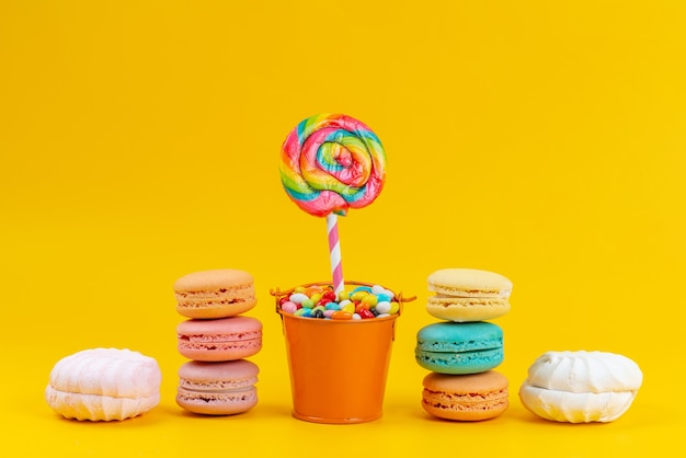 Una vista frontale francese macarons insieme a meringhe e lecca-lecca su giallo, dolci biscotti torta