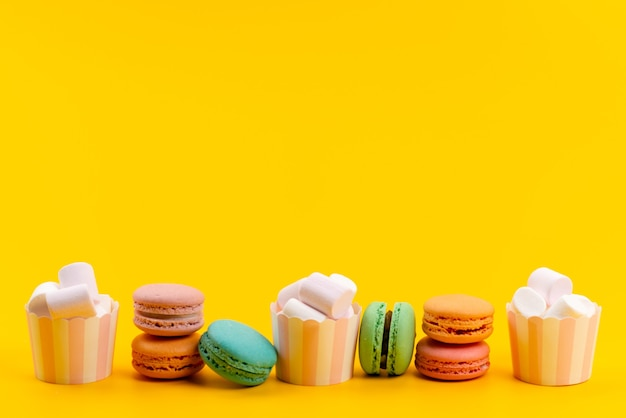 A front view french macarons along with white, marshmallows isolated on yellow, cake sweets confectionery