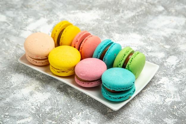 Vista frontale francese macarons torte colorate su superficie bianca torta torta zucchero cuocere biscotti dolci biscotti