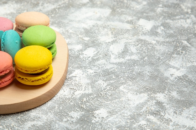 Front view french macarons colorful cakes on the white surface cake pie sugar biscuit sweet cookies