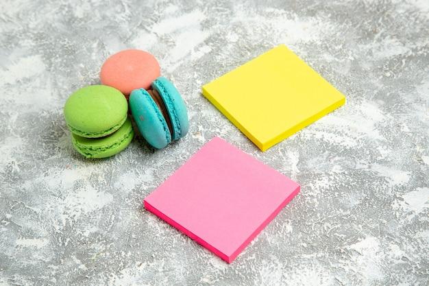 Vista frontale francese macarons torte colorate con adesivi su superficie bianca torta torta zucchero cuocere biscotti dolci biscotti