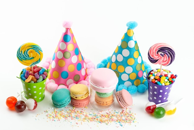Una vista frontale francese macarons caramelle colorate e lecca-lecca insieme a divertenti protezioni di compleanno su bianco, celebrazione colore zucchero dolce