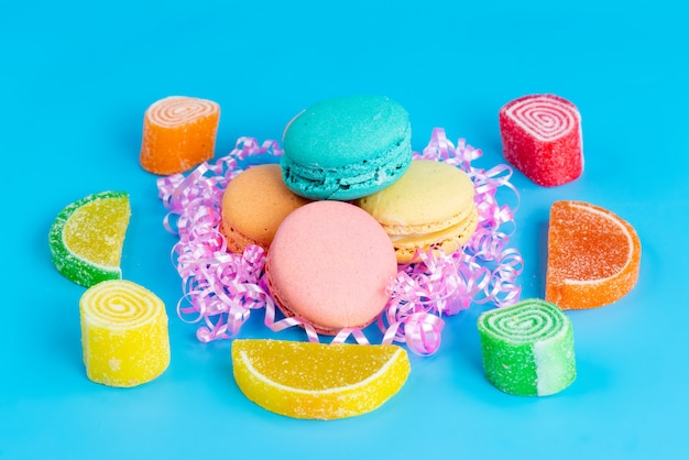 A front view french macarons colorful sweet yummy along with confitures on blue