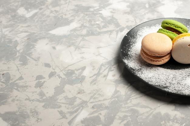 Vista frontale macarons francesi deliziose torte colorate all'interno della piastra sulla superficie bianca