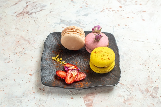 Macarons francesi di vista frontale all'interno del piatto sulla torta dolce del biscotto della tavola bianca