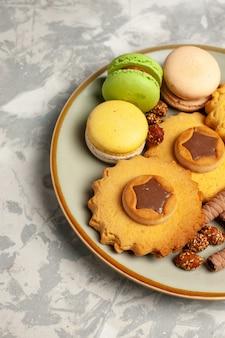 Macarons francesi di vista frontale con torte e biscotti sulla superficie bianca