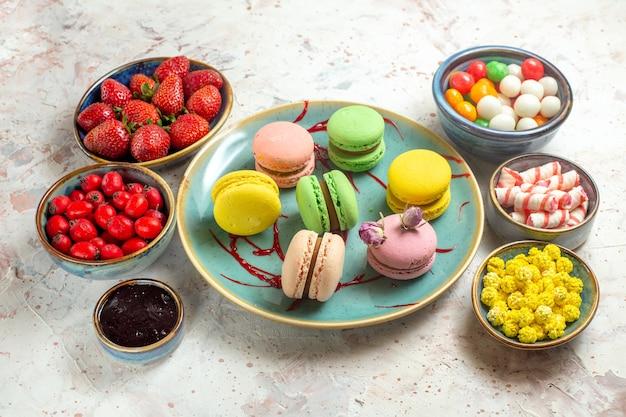 Macarons francesi di vista frontale con le caramelle e le bacche sulla torta bianca del biscotto del biscotto della tavola