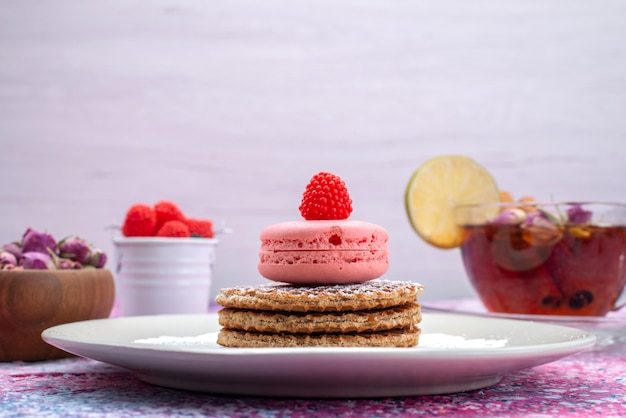 Front view french macarons with cinnamon berries and tea