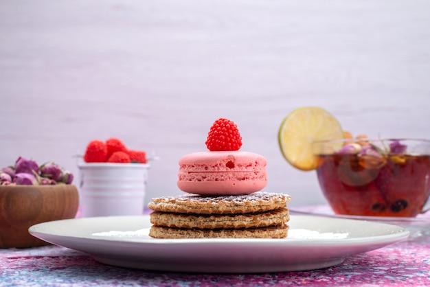 Macarons francesi di vista frontale con bacche e tè alla cannella