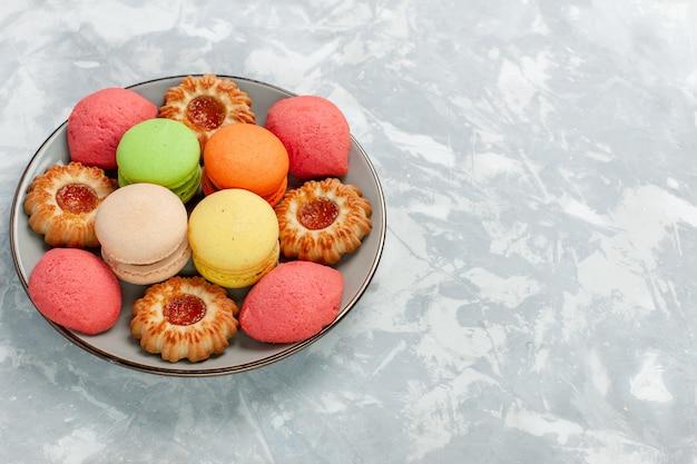 Macarons francesi di vista frontale con i biscotti sulla superficie bianca chiara cuocere lo zucchero del biscotto della torta dolce