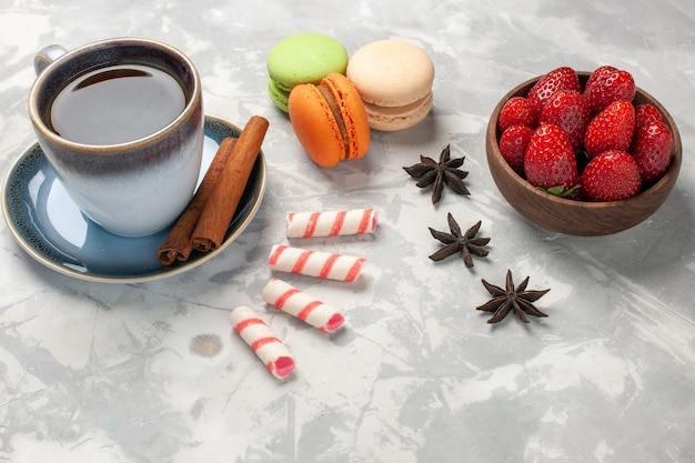 Вид спереди французские макароны с чашкой чая и свежей красной клубникой на белой поверхности торта, сахарного бисквита, сладкого печенья