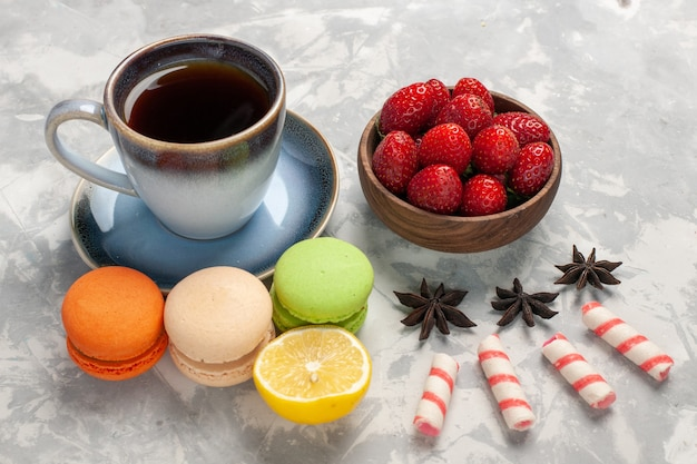 Вид спереди французские макароны с чашкой чая на белом столе, торт, бисквит, сахарный пирог, сладкое печенье
