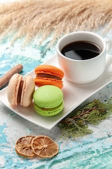 Macarons francesi di vista frontale con una tazza di tè sulla superficie blu