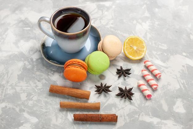 Macarons francesi di vista frontale con la tazza di tè sul biscotto dolce della torta di zucchero della torta di superficie bianca