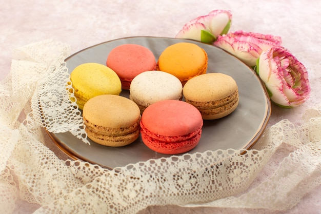 A front view french macarons with flower on the pink desk