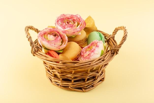 Un macarons francesi di vista frontale con i fiori all'interno del canestro sul dolce giallo dello zucchero della torta del biscotto dello scrittorio
