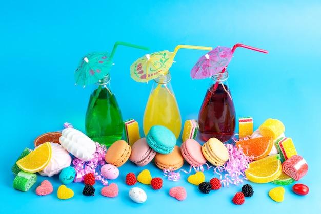Macarons francesi di una vista frontale con le marmellate e i marshmallow freschi dei cocktail sull'azzurro