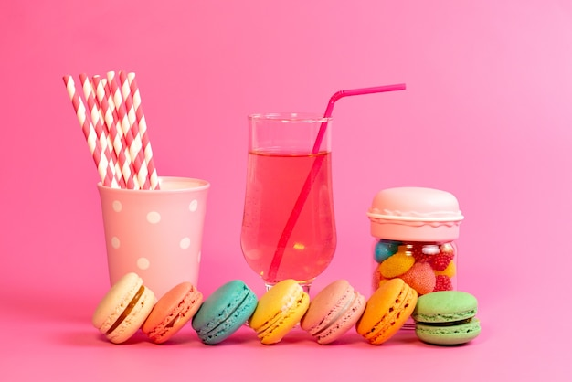 A front view french macarons with fresh drink colorful candies and stick candies on pink, cake biscuit confectionery