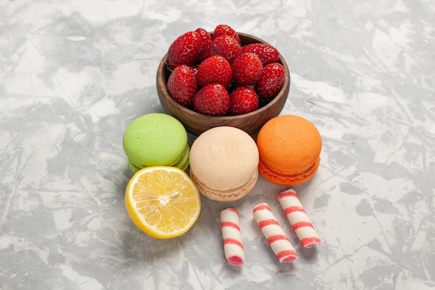 Macarons francesi di vista frontale con le fragole fresche sullo zucchero dolce del biscotto della torta della bacca dei frutti di superficie bianca
